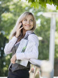 Empresaria que se coloca al aire libre con el teléfono celular y los documentos comerciales foto de archivo libre de regalías