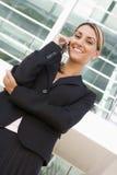 Empresaria que se coloca al aire libre en el teléfono móvil Foto de archivo libre de regalías