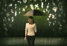 Empresaria que se coloca con el paraguas y el llover de los números 3d concentrado Fotos de archivo