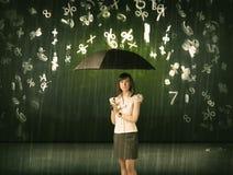 Empresaria que se coloca con el paraguas y el llover de los números 3d concentrado Imagen de archivo libre de regalías