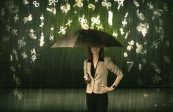 Empresaria que se coloca con el paraguas y el llover de los números 3d concentrado Fotos de archivo libres de regalías