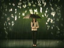Empresaria que se coloca con el paraguas y el llover de los números 3d concentrado Imagenes de archivo