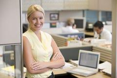 Empresaria que se coloca en la sonrisa del cubículo imagen de archivo