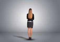 Empresaria que se coloca en un cuarto gris vacío rear Imagen de archivo libre de regalías