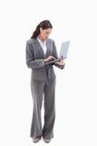 Empresaria que se coloca y que pulsa en una computadora portátil Imagenes de archivo