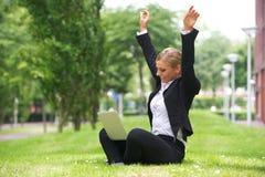 Empresaria que se sienta al aire libre con el ordenador portátil y los brazos para arriba en la celebración Foto de archivo