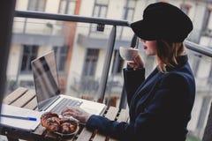 Empresaria que se sienta cerca de una tabla en tiempo de desayuno Fotografía de archivo libre de regalías