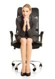 Empresaria que se sienta con las manos en la barbilla imagen de archivo libre de regalías