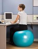 Empresaria que se sienta en bola del ejercicio en el escritorio Imágenes de archivo libres de regalías