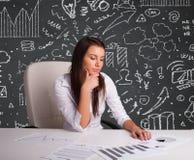 Empresaria que se sienta en el escritorio con esquema y los iconos del negocio Imágenes de archivo libres de regalías