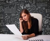 Empresaria que se sienta en el escritorio con esquema y los iconos del negocio Fotografía de archivo libre de regalías