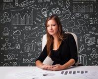 Empresaria que se sienta en el escritorio con esquema y los iconos del negocio Foto de archivo