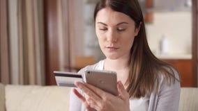 Empresaria que se sienta en el sofá en la sala de estar que compra en línea con la tarjeta de crédito en smartphone metrajes