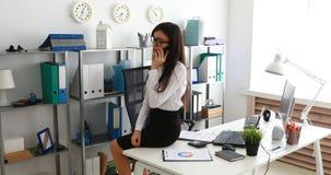 Empresaria que se sienta en la tabla blanca y que habla en smartphone en oficina moderna almacen de video