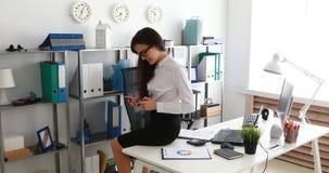 Empresaria que se sienta en la tabla blanca y que usa smartphone en oficina moderna metrajes