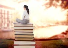 Empresaria que se sienta en los libros apilados por el agua Imagen de archivo