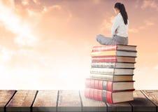 Empresaria que se sienta en los libros apilados por las nubes soleadas Foto de archivo libre de regalías