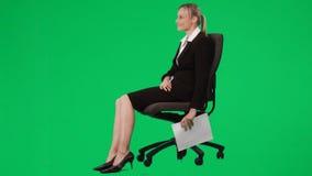 Empresaria que se sienta en notas de una escritura de la silla contra la pantalla verde