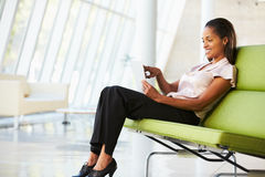 Empresaria que se sienta en oficina moderna usando la tablilla de Digitaces Imagen de archivo