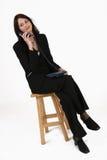 Empresaria que se sienta en silla y que escucha el llamante Imagen de archivo