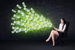 Empresaria que se sienta en tableta de la tenencia de la silla con los billetes de dólar Foto de archivo