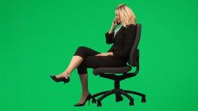 Empresaria que se sienta en una silla en el teléfono contra la cantidad verde de la pantalla almacen de video