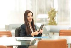 Empresaria que se sienta en una tabla en la oficina que lee una tableta con una sonrisa contenta Imágenes de archivo libres de regalías