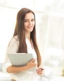 Empresaria que se sienta en una tabla en la oficina que lee una tableta con una sonrisa contenta Fotos de archivo libres de regalías