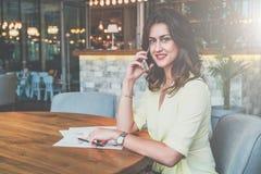 Empresaria que se sienta solamente en la tabla en café y que llama por el teléfono celular lifestyle Imagen de archivo libre de regalías