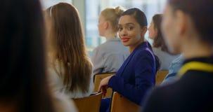 Empresaria que se sienta y que sonríe en el seminario 4k del negocio almacen de video