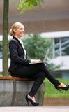 Empresaria que sonríe y que trabaja al aire libre en el ordenador portátil Fotografía de archivo libre de regalías