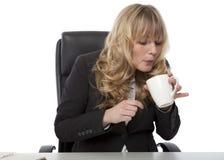 Empresaria que sopla en una taza de café caliente Imagen de archivo libre de regalías