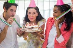 Empresaria que sopla hacia fuera velas en la torta Imágenes de archivo libres de regalías