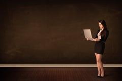 Empresaria que sostiene el ordenador portátil de alta tecnología en fondo con el copysp Foto de archivo