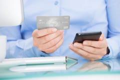 Empresaria que sostiene el teléfono móvil y la tarjeta de crédito fotografía de archivo