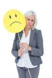Empresaria que sostiene la cara sonriente triste Fotos de archivo libres de regalías