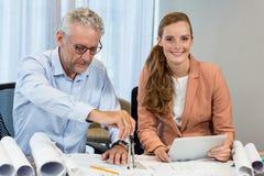 Empresaria que sostiene la tableta digital mientras que compañero de trabajo que trabaja en modelo con el compás Fotos de archivo libres de regalías