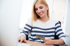 Empresaria que sostiene la tarjeta de banco y que mecanografía en el teclado Imagen de archivo libre de regalías