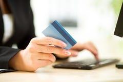 Empresaria que sostiene la tarjeta de crédito en el ordenador portátil para el concepto en línea del pago Foto de archivo libre de regalías