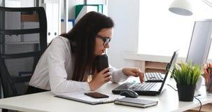 Empresaria que sostiene la taza de café y que bosteza en oficina almacen de metraje de vídeo