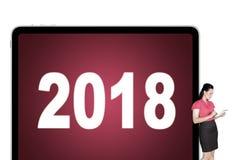 Empresaria que sostiene una tableta digital que se inclina 2018 en la cartelera foto de archivo libre de regalías