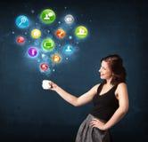 Empresaria que sostiene una taza blanca con los iconos del ajuste Fotos de archivo libres de regalías