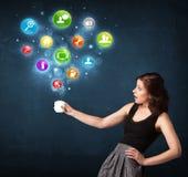 Empresaria que sostiene una taza blanca con los iconos del ajuste Imágenes de archivo libres de regalías