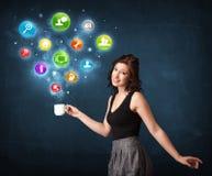 Empresaria que sostiene una taza blanca con los iconos del ajuste Fotografía de archivo libre de regalías