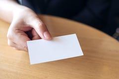 Empresaria que sostiene y que da una tarjeta de visita vacía alguien en la tabla imagen de archivo