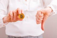 Empresaria que sujeta la moneda y el pulgar de oro del bitcoin hacia abajo Fotos de archivo