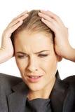 Empresaria que tiene dolor de cabeza enorme Imagen de archivo libre de regalías