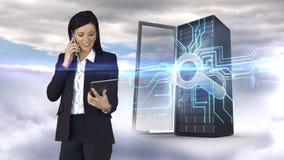 Empresaria que tiene llamada de teléfono y que sostiene la tableta delante de la torre del servidor almacen de video