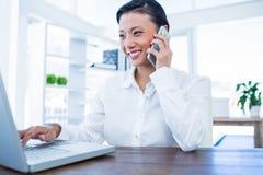 Empresaria que tiene llamada de teléfono y que usa el ordenador portátil Imagen de archivo