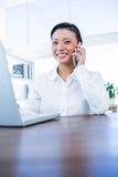 Empresaria que tiene llamada de teléfono y que usa el ordenador portátil Foto de archivo